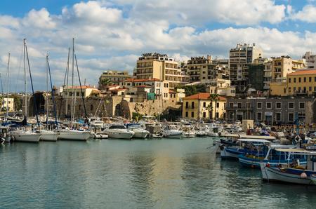 HERAKLION, GREECE - November, 2017: colorful greek fishing boats, fishing nets and yachts near the old Venetian fortress Koule, Heraklion port, Crete
