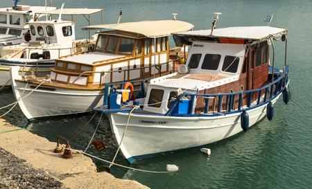 HERAKLION, GREECE - November, 2017: colorful greek traditiona fishing boats moored to a pier in Heraklion port, near old Venetian fortress Koule, Crete Editorial