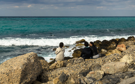 HERAKLION, GREECE - November, 2017: In the foreground there are tourists, resting on rocks near the sea, in the background - Aegean Sea, waves that run into the rocks, old Venetian fortress Koule, Heraklion port, Crete Editorial