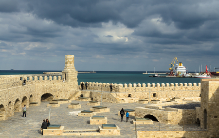 HERAKLION, GREECE - November, 2017:Tourists visiting old Venetian Fortress Koule in Heraklion, in the Rays of the setting sun against a stormy sky, Crete
