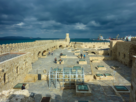 HERAKLION, GREECE - November, 2017: Tourists visiting old Venetian Fortress Koule in Heraklion, in the Rays of the setting sun against a stormy sky, Crete Editorial
