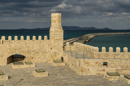 Old Venetian Fortress Koule in Heraklion, Crete in the Rays of the setting sun against the stormy sky, Aegean sea and the mountain range, Crete