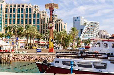EILAT, ISRAEL - November 7, 2017: entrance to marina, with promenades, modern hotel complexes, palms, boats, cafes, restaurants and shopping centers. Eilat - famous resort and recreational city in Israel
