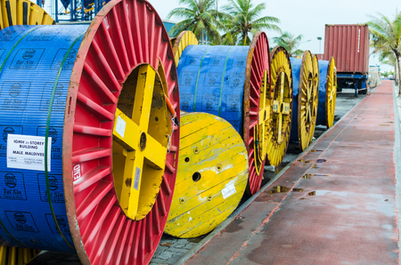 MALE, MALDIVES - November 16, 2017: Close-up - large multi-colored coils for electric cables, lying in the row along the road, Male, Maldives. Redakční