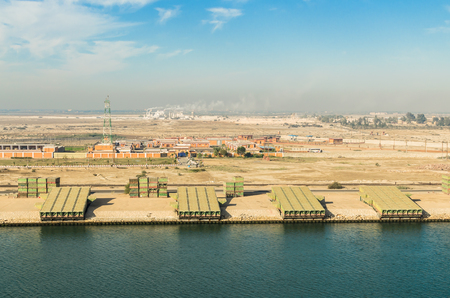 Industry along the side of the Suez canal: in the foreground of industrial buildings, in the background - the railway, palm trees and buildings. View from the water, Suez Canal, Egypt Stock Photo