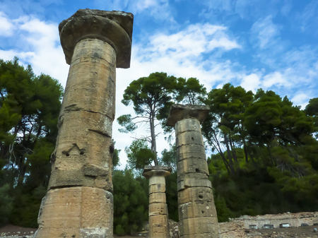 Pillars of marble against a blue sky and clouds. Bottom view. Olympia, Peloponnes, Greece