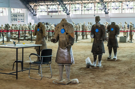 XIAN, SHANXI, CHINA - October 16, 2013: soldiers of the terracotta army during restoration work. Terracotta Army is a collection of terracotta sculptures depicting armies of Qin Shi Huang, the first Emperor of China. Hian, China