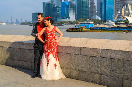 SHANGHAI, CHINA - October 26, 2013: Young couple at the Bund. It is a waterfront area of central Shanghai, which runs along the Huangpu River, facing Pudong skyscrapers, Shanghai, China