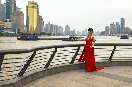 SHANGHAI, CHINA - October 26, 2013: Chinese woman in red dress at the Bund. It is a waterfront area of central Shanghai, which runs along the Huangpu River, facing Pudong skyscrapers, Shanghai, China