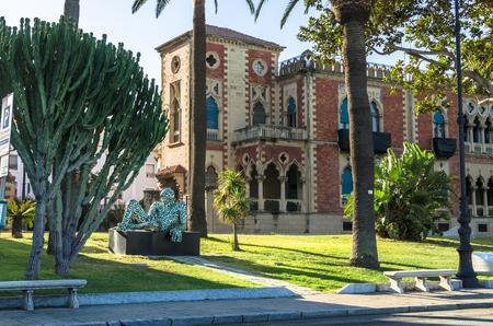Reggio Calabria, Italy - October 30, 2017: Modern sculpture of artist Paola Epifani (Rabarama) and Neo-gothic style villa Genoese-Zerbi, Reggio Calabria, southern Italy