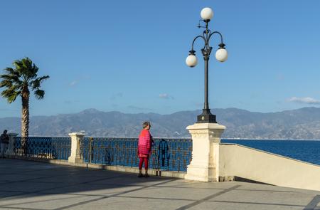 Reggio Calabria, Italy - October 30, 2017: View of the Reggio di Calabria promenade Lungomare Falcomata and Strait of Messina connected Mediterranean and Tyrrhenian sea and Sicilia island background, Reggio Calabria, Italy Редакционное