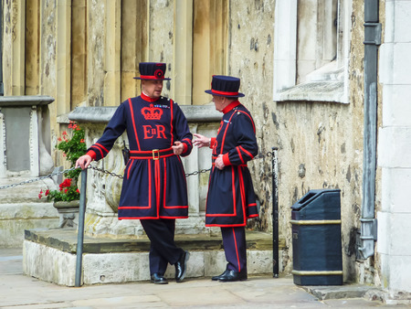 London, England – July 14, 2011: Two guards of Tower of London and the king (beef eater) in a bright red uniform of Tudor era, standing at entrance of vault of royal treasures, London, UK.