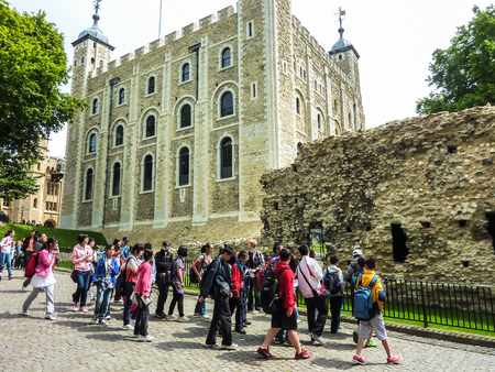 London, England – July 14, 2011: Many tourists visiting ancient White Tower of London and royal treasure vault in a sunny day. London, UK. Tower was built by William the Conqueror in 1240, provided accommodation for  king and his representatives.
