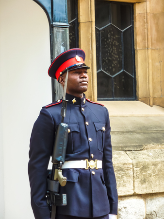 London, England – July 14, 2011: Palace guard in traditional national form with honor and dignity guarding the entrance to the vault of royal treasures, Tower of London, UK. Редакционное