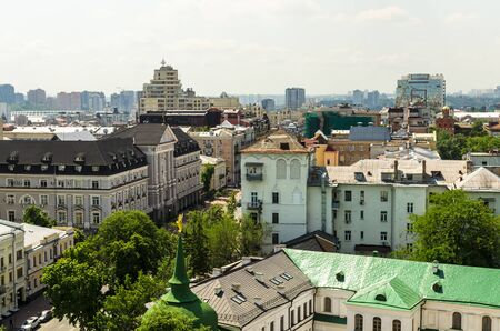 Aerial view from St. Sophia Cathedral on buildings of historical center of Kiev. Beautiful Kiev roofs. In  background - modern buildings of Kiev. Kiev - capital of Ukraine