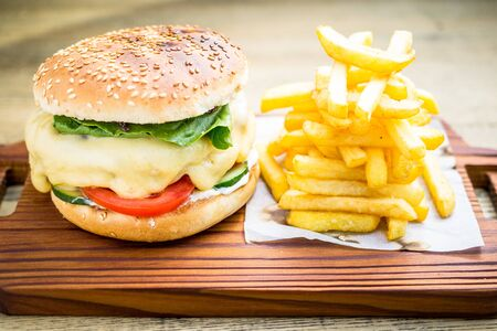 Fresh cheeseburger with melting cheese, tomatoes, cucumber, lettuce, homemade sauce and french fries