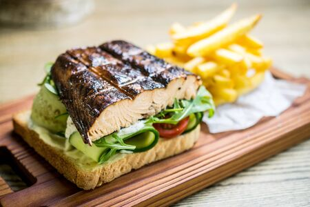 Grilled fish sandwich with cucumbers, cherry tomatoes, lettuce, toasted bread, sauce and french fries