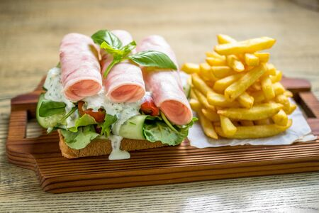 Rolled ham sandwich with fresh dill sauce, cucumbers, cherry tomatoes, lettuce and french fries