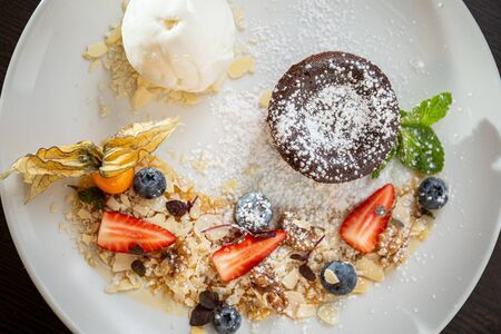 Chocolate fondant with vanilla ice cream, almond crumbs and fresh strawberries, blueberries and other forest berries