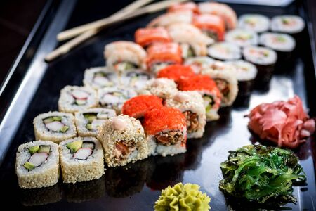 Sushi set with various maki and uramaki sushi types on plates 免版税图像