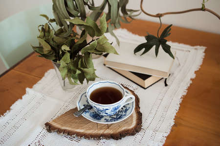 themed coffee corner with dried eucaliptus and bay leaves and retro tablecloth, autumn vibes, bohemian porcelain ornamental mug on the wooden cut with the bark, books in the background Banque d'images