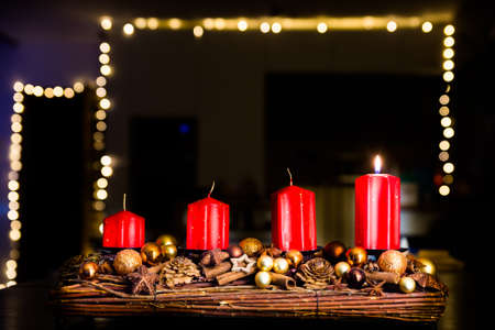 Four red candles - the first lighted candle of the first Sunday of Advent festival before Christmas with lightning chain in background