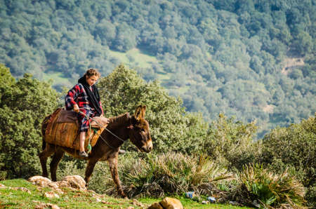 Azrou, Morocco - April 09, 2015. Young cute berber girl riding on the donkey in mountain