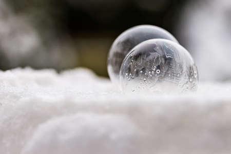 Two frozen soap bubbles freezing of low temperature under zero on snow