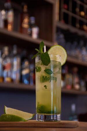 Cuban mojito drink with lemon mint and good herb on a wooden base with a bar background