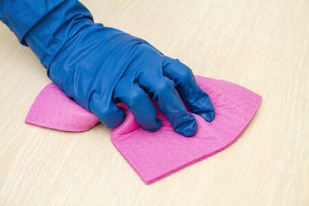 A human hand in a protective glove disinfects the table with a cleaning cloth for viruses prevention