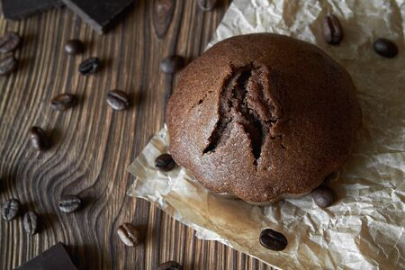 One homemade chocolate muffin on parchment with coffee beans and pieces of chocolate. Dark wooden background, closeup, top view 免版税图像