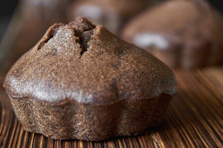 Homemade coffee muffin on a wooden board with a group of chocolate cupcakes on dark wooden background. Closeup, selective focus 免版税图像