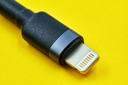 Black micro USB type c data and power cable plug on yellow background. Closeup Banco de Imagens