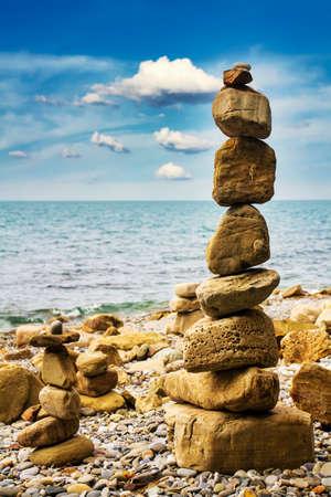 Pyramid of sea stones on the seashore at the pebble beach. Concept of harmony and balance. Imagens
