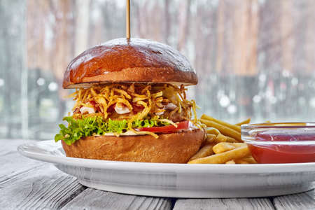 Hamburger with chicken cutlet, cheese, french fries, tomato, salad, sauce and ketchup on a white plate and a light wooden background Zdjęcie Seryjne