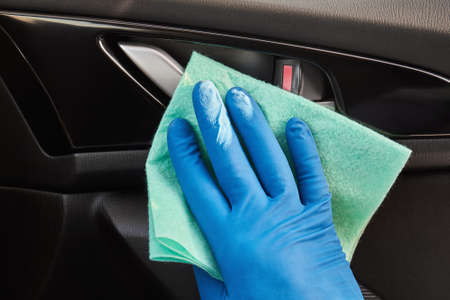 Hand of man in blue protective glove is wiping with a cloth an interior handle of car door.
