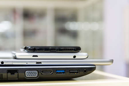 Modern computer gadgets are on the store shelf. Smartphones and tablet are on the laptop. Side view, closeup, selective focus