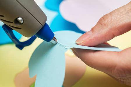 Woman uses hot melt glue gun in handmade applications. Closeup, selective focus