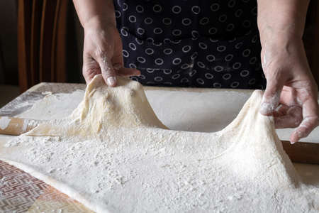 Senior woman stretches the dough during rolling out dough in her home kitchen. Homemade noodle or pasta production by grandma. Closeup, selective focus
