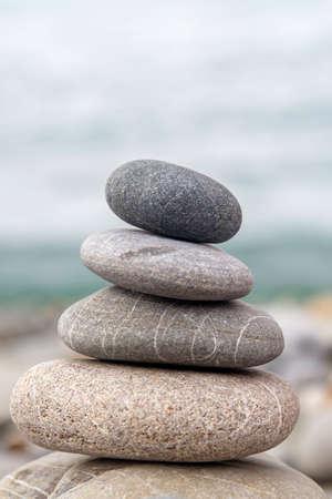 Pyramid of sea stones on the seashore at the pebble beach. Concept of harmony and balance. Stock Photo