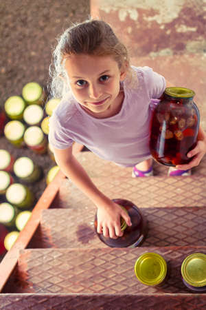 A girl takes big glass jars of homemade strawberry compote from the cellar