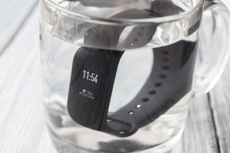 Black fitness watch (activity tracker), fitness bracelet, tracker with time and steps on display in the glass of water. Closeup, selective focus