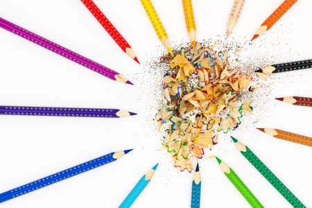 Multicolored pencils on a light background next to planer and pencil shavings. Top view