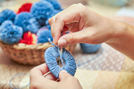 Handmade pompons. The process of making pompons from threads by woman