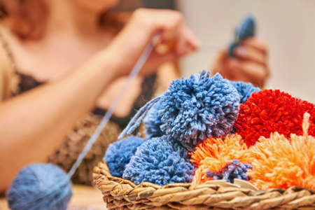A basket with handmade pompons. The process of making pompons from threads by woman on the background.