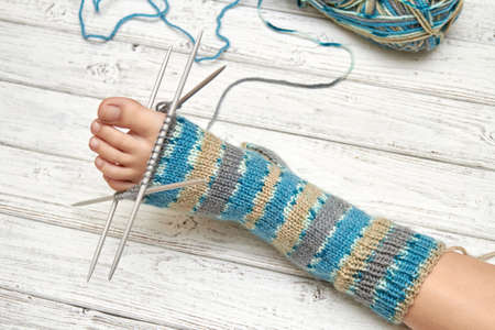 Try on sock on a baby foot while knitting. Light wooden background, selective focus
