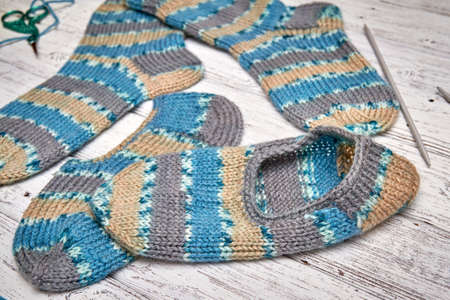 Two children's knitted socks and slippers on a light wooden background 스톡 콘텐츠