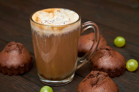 A cup of iced coffee with homemade chocolate muffins and grapes on dark wooden background. Closeup, selective focus 免版税图像
