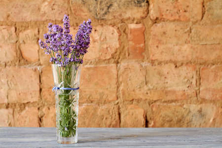 Bouquet of fresh purple lavender in a glass vase on the brick wall background