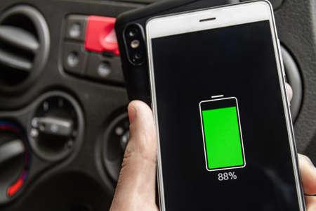 Phone battery wireless charge sharing technology. Wireless charge sharing smartphone in the car in rainy weather Reklamní fotografie